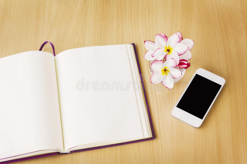 Smartphone and blank note book or diary in relax mood, empty not. E book or diary with frangipani or plumeria on work table, blank page diary memorandum and royalty free stock photos