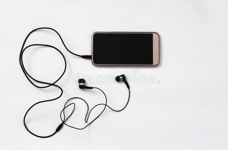 Smartphone with blank screen connects to headphones with spiral cable on white background top view.  royalty free stock photo