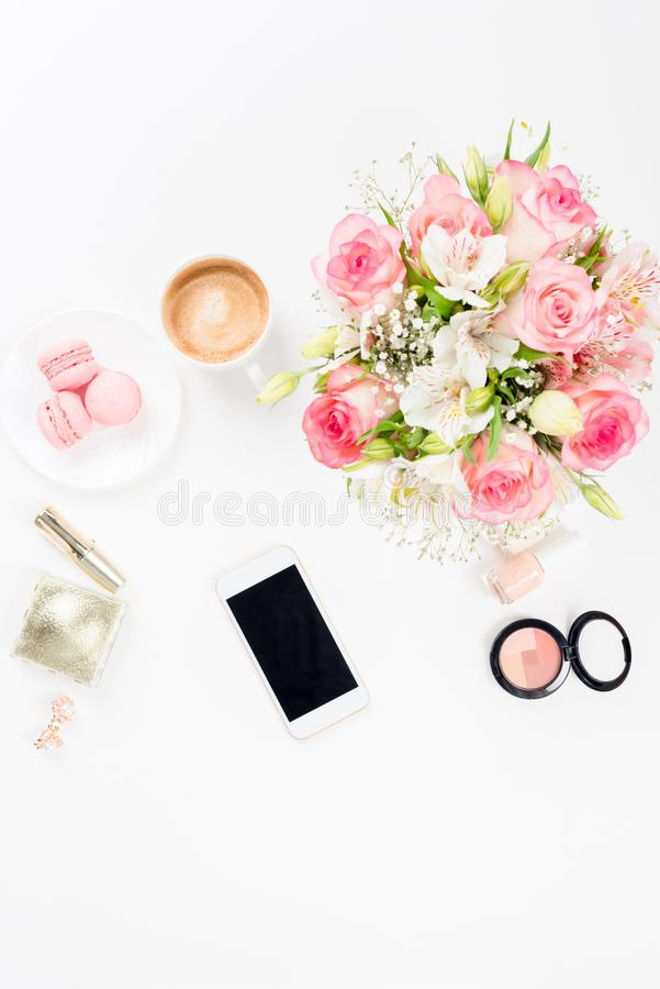 Smartphone with blank screen, cosmetics and beautiful blooming flowers on white. Top view of smartphone with blank screen, cosmetics and beautiful blooming stock photography