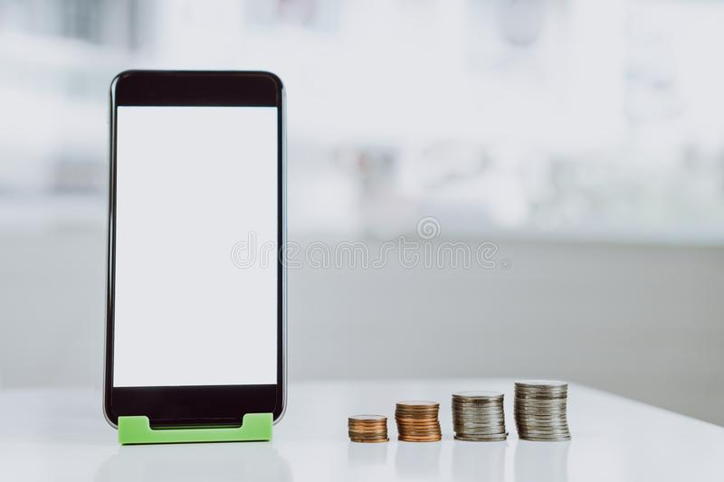 Smartphone blank screen placed on a vertical green stand, and the coins are arranged in a row. Represents the growth of financial royalty free stock photography