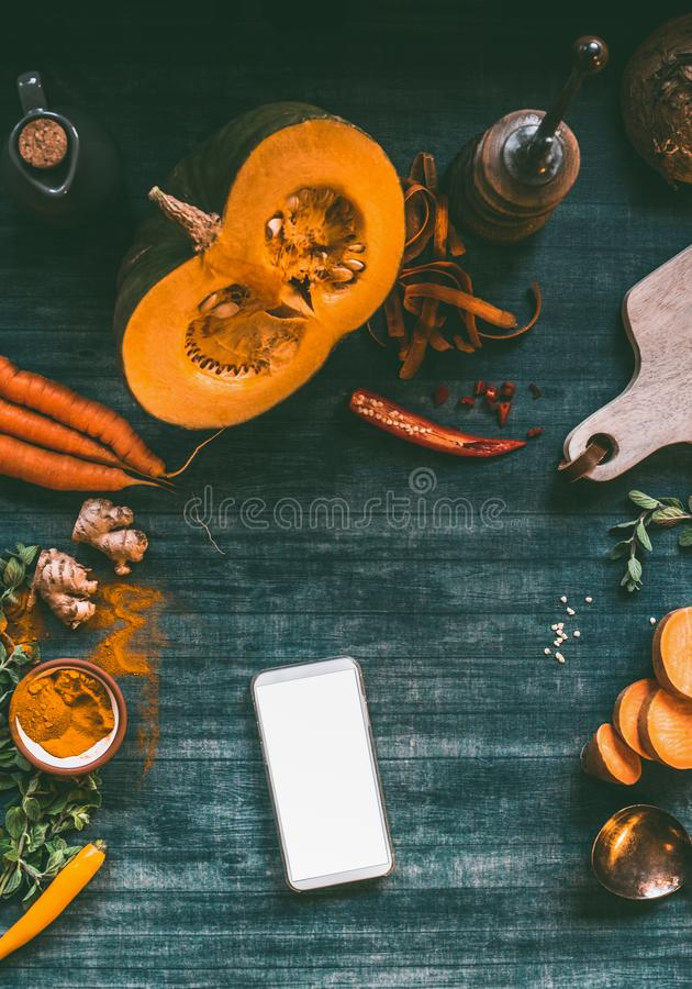 Smartphone with blank white screen mock up on kitchen tables with pumpkin and cooking ingredients, top view. Blog, online shopping stock photo