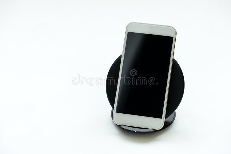 Smartphone branco carregado pelo carregador sem fio no fundo de madeira branco Conceito da carga sem fio ou da tecnologia digital imagem de stock