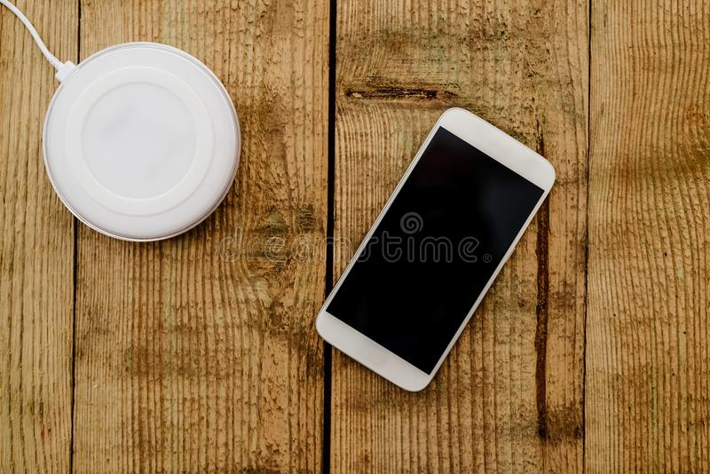Smartphone branco e almofada de carregamento fotografia de stock
