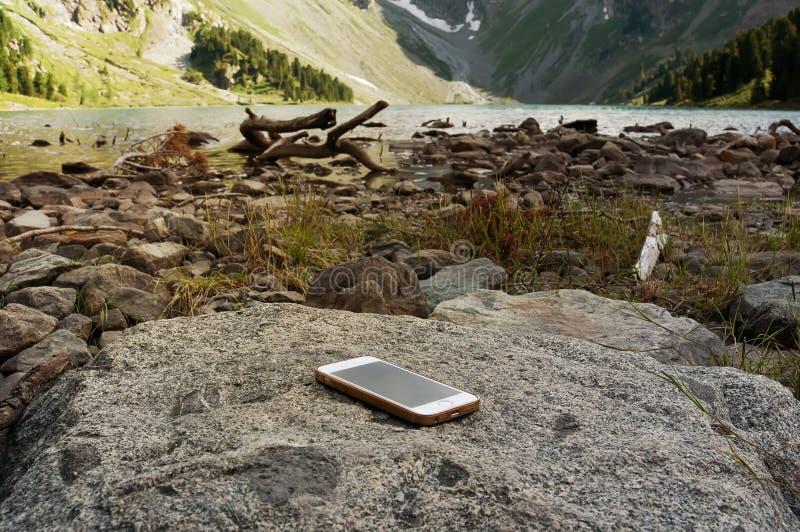 Smartphone branco esquecido em uma rocha imagens de stock