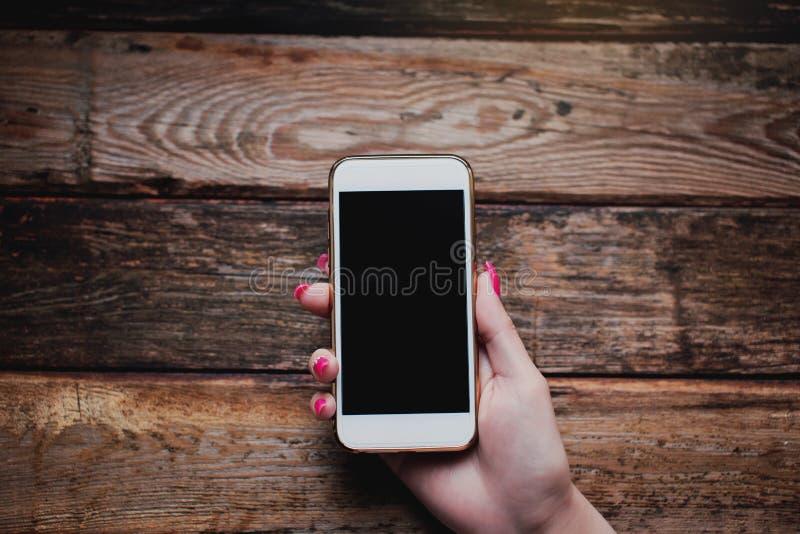 Smartphone branco nas mãos fêmeas em um fundo de madeira fotos de stock royalty free