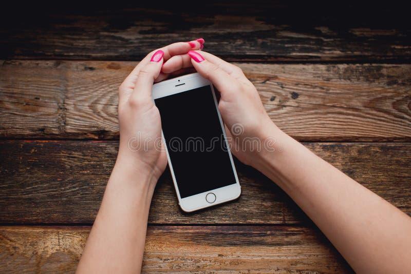 Smartphone branco nas mãos fêmeas em um fundo de madeira fotografia de stock