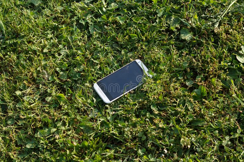 Smartphone branco perdido que encontra-se na grama imagens de stock