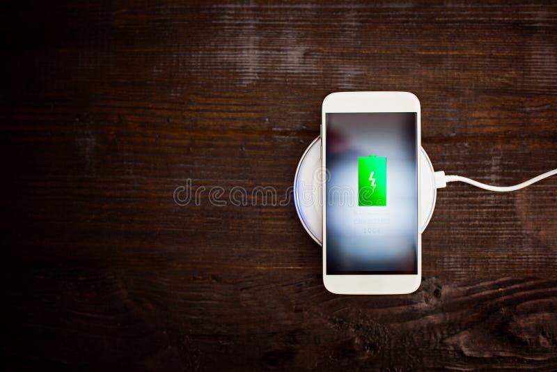 Smartphone branco que carrega em uma almofada de carregamento fotos de stock