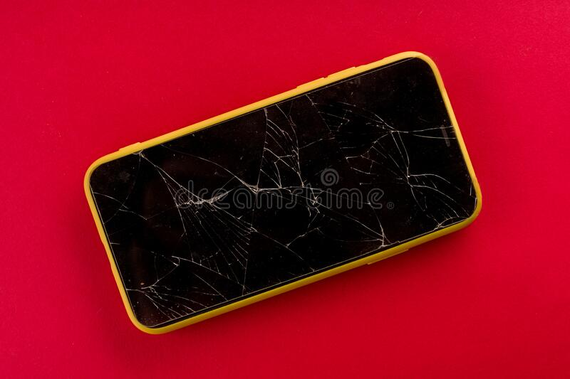 Smartphone with broken screen on red background. Image, cellphone, mobile, isolated, display, smashed, glass, crack, repair, accident, crash, white, damaged royalty free stock images