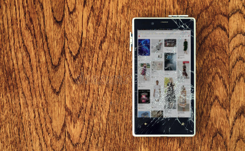 Smartphone with broken screen on wooden table. royalty free stock photography
