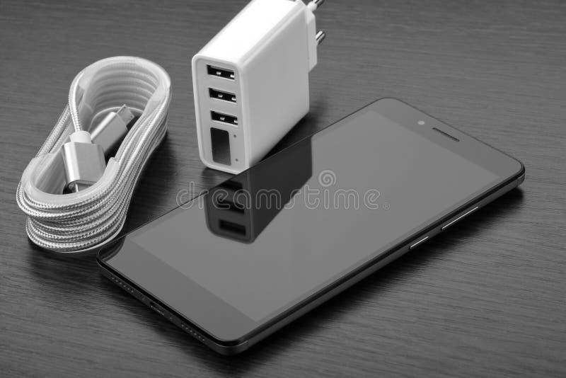 Smartphone, carregador branco com três porta usb e cabo trançado na bobina em uma tabela de madeira imagem de stock royalty free