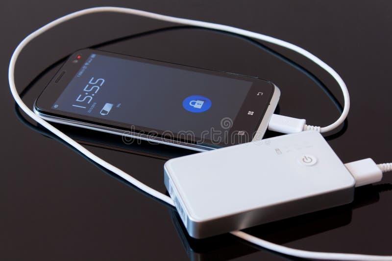 Smartphone a chargé par la banque de puissance photos stock
