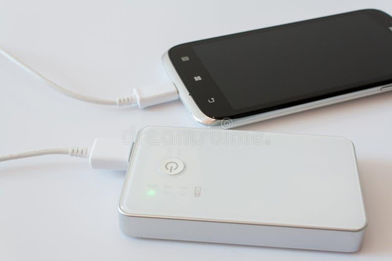 Smartphone a chargé par la banque de puissance photographie stock