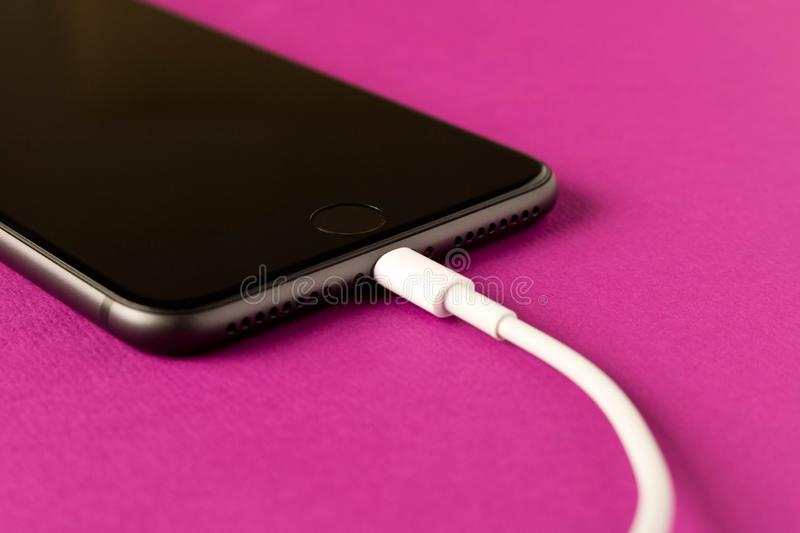 Smartphone on charge . On a purple background. Close up royalty free stock photography
