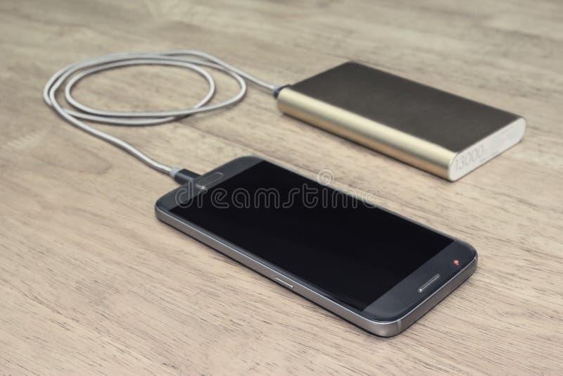 Smartphone chargeant de la banque de puissance sur le fond en bois, effet de filtre images libres de droits