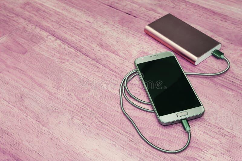 Smartphone chargeant de la banque de puissance sur le fond en bois, effet de filtre photo libre de droits