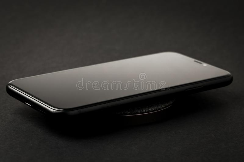 Smartphone is charged by a wireless charger on a black background. The concept of new technologies royalty free stock image