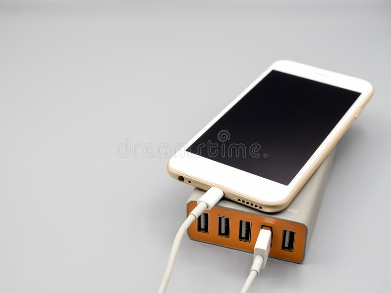 Smartphone charging with multiport USB power adaptor. Smart phone charging with multiport USB power adaptor on gray background with copy space, Selective focus stock photography