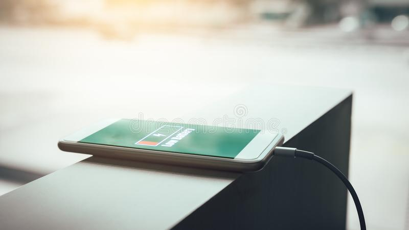Smartphone charging at office room. stock photo
