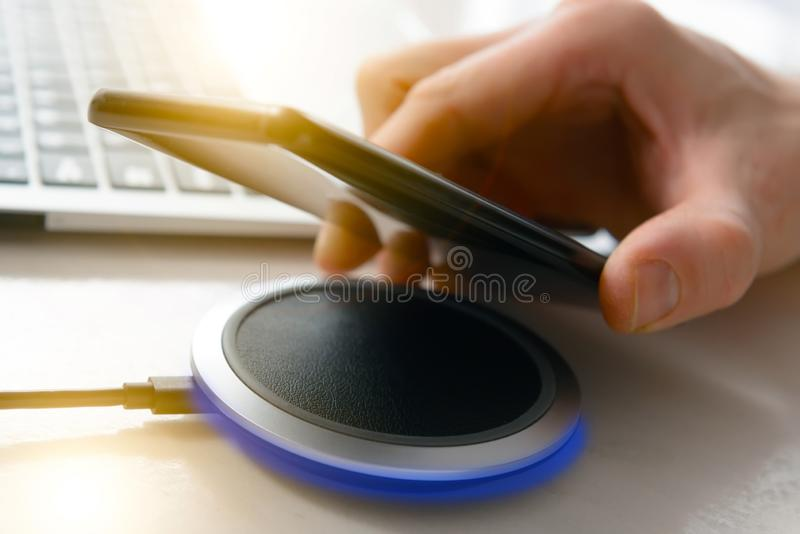 Smartphone charging on a wireless charger stock image