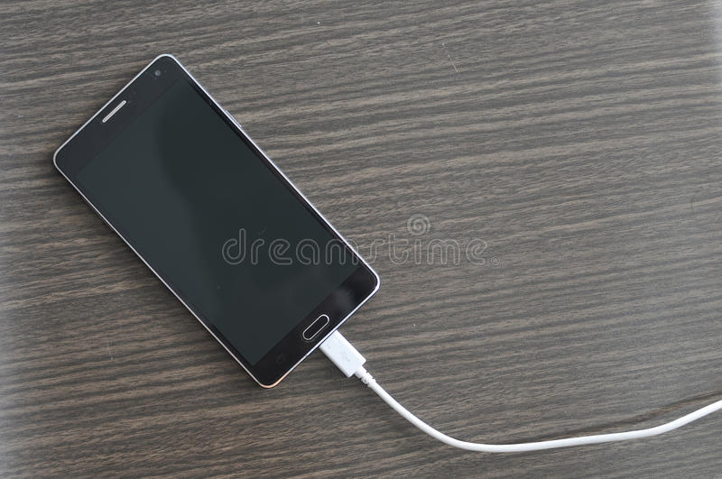 Smartphone Charging On Wood Table stock images