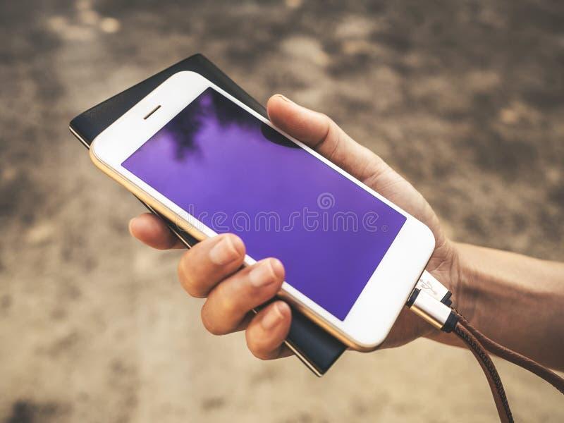 Smartphone che carica batteria dalla banca di potere esterno immagine stock