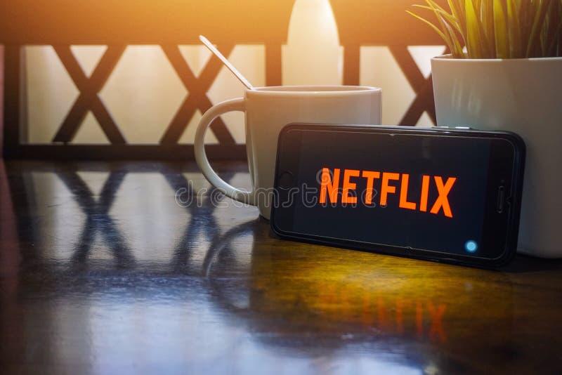 Smartphone che visualizza parola Netflix sulla tavola di legno con il frammento del raccolto e del fuoco selettivo fotografia stock
