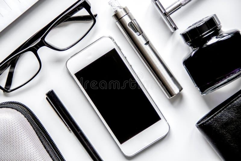 Smartphone, cigarro eletrônico e opinião superior dos acessórios do ` s dos homens imagem de stock