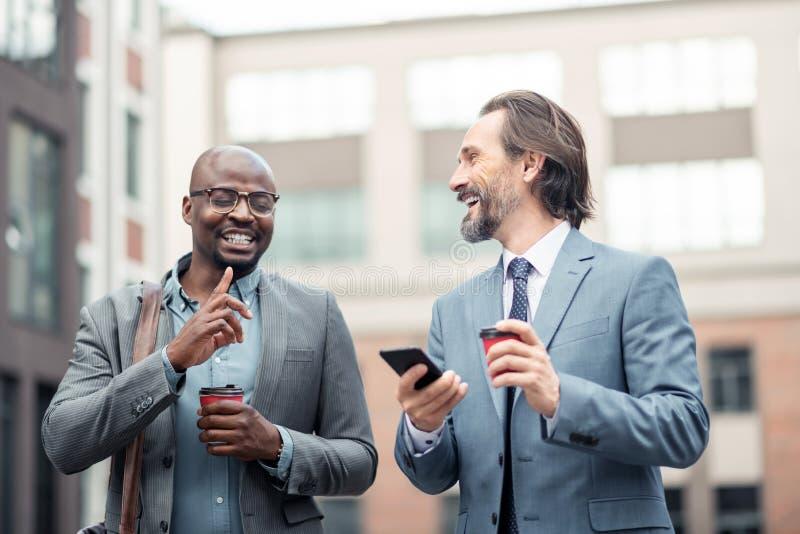 smartphone Cinzento-de cabelo da terra arrendada do homem de negócios que fala ao colega imagem de stock