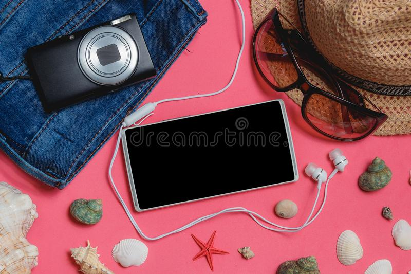 Smartphone, Clothes, Sunglasses, Photo Camera, Brown Hat, on Pink Background. Top View Travel Concept Mock up. Smartphone, Clothes, Sunglasses, Photo Camera royalty free stock photo