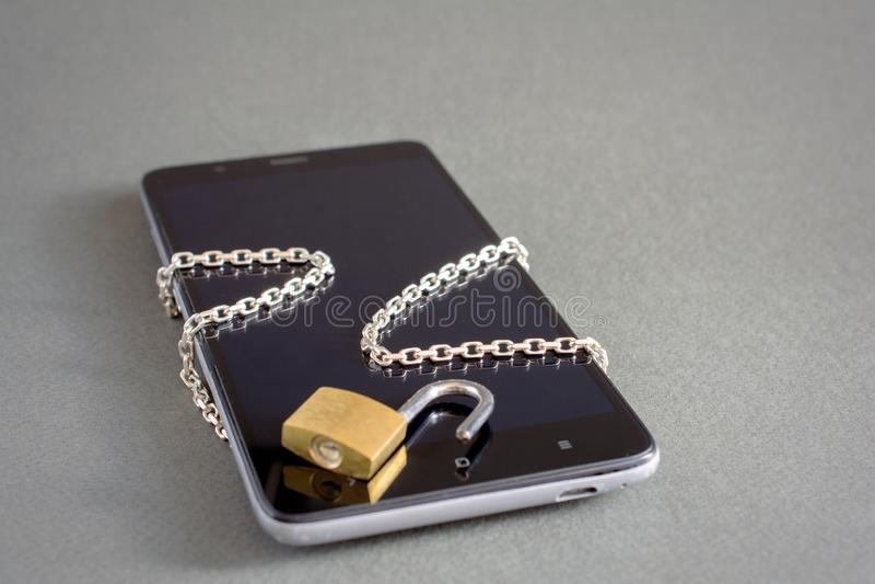 Smartphone com destrava a corrente do cadeado foto de stock