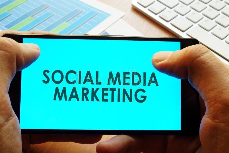 Smartphone com mercado social dos meios das palavras foto de stock