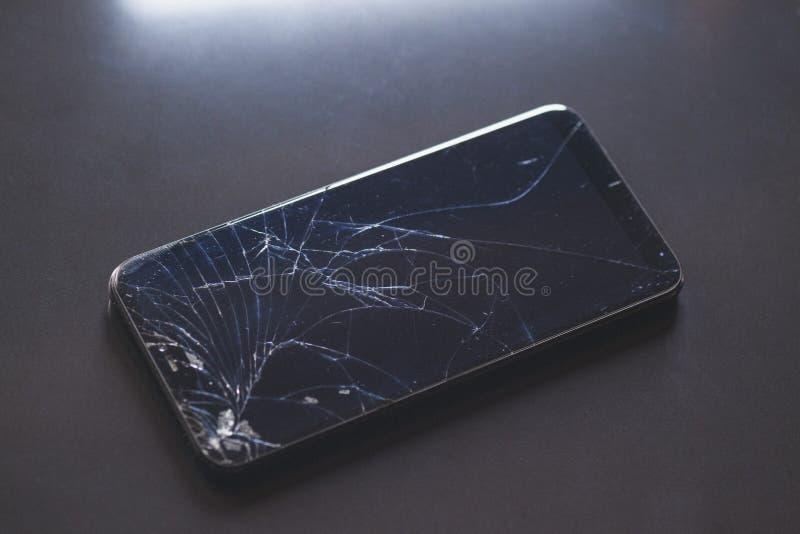 Smartphone com o ?cran sens?vel quebrado no desktop preto fotografia de stock royalty free