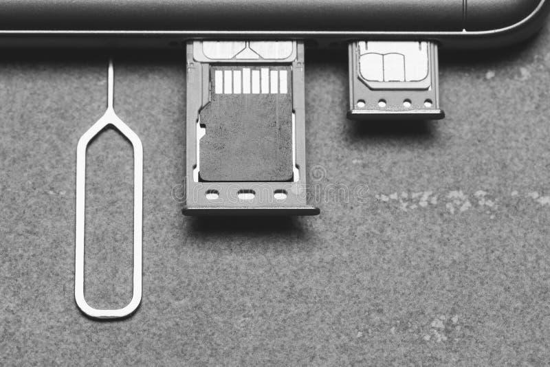 Smartphone com os entalhes abertos de SIM e micro memória do SD em um fundo cinzento com espaço da cópia, close-up da vista super imagens de stock royalty free