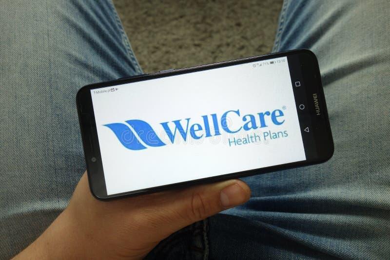 Smartphone com planos da saúde de WellCare, Inc da terra arrendada do homem logo fotos de stock royalty free