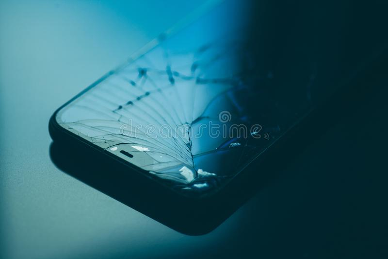 Smartphone com a tela quebrada no desktop preto fotografia de stock royalty free