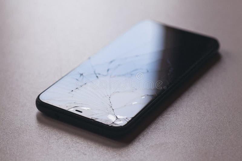 Smartphone com a tela quebrada no desktop preto fotografia de stock