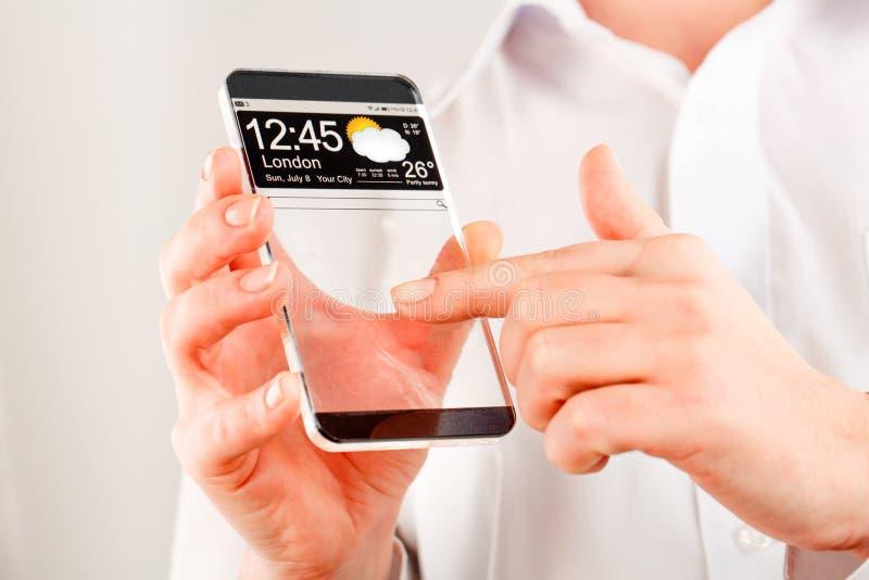 Smartphone com a tela transparente nas mãos humanas. imagens de stock royalty free