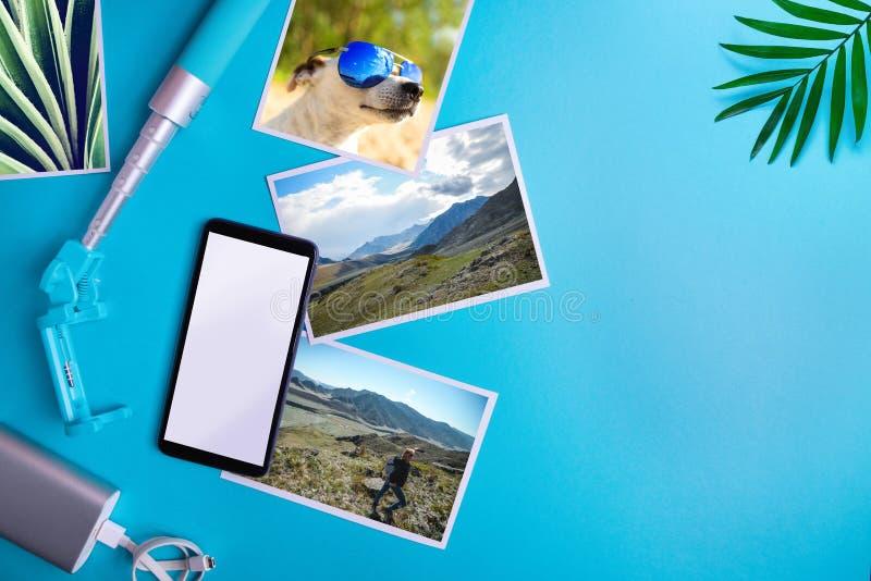 Smartphone com tela vazia, insetos, fotos no fundo azul Modelo, conceito colocado liso das férias fotografia de stock