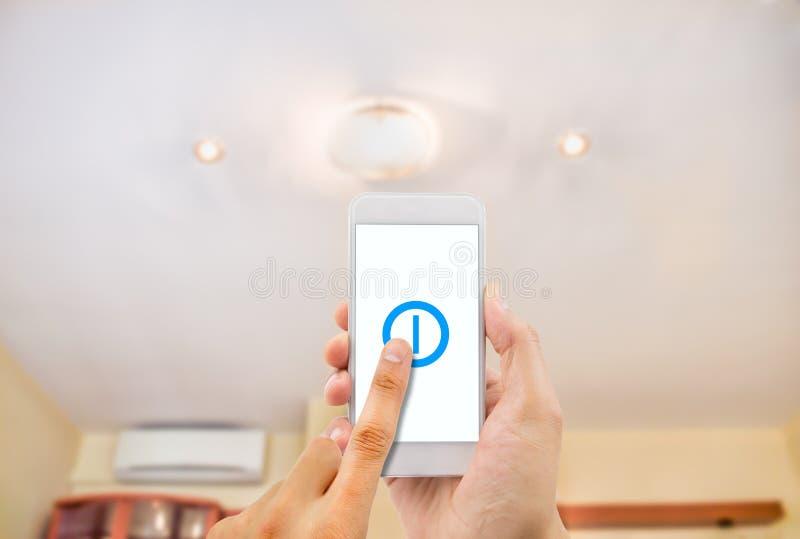 Smartphone commandant une lumière images stock
