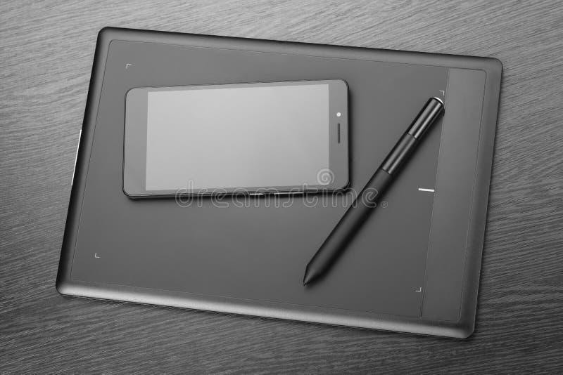 Smartphone, comprimé graphique et stylet sur une table en bois Détails de lieu de travail d'un concepteur numérique d'art de grap image stock