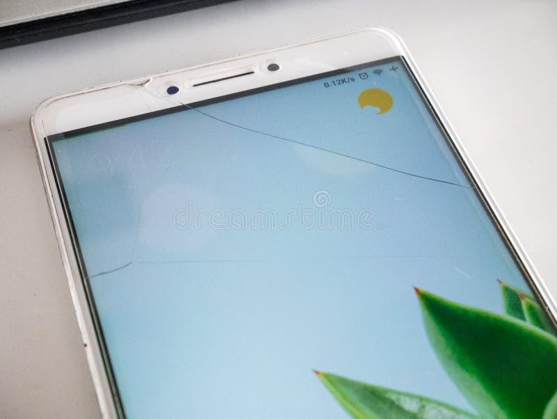 Smartphone con la pantalla de cristal moderada agrietada imagen de archivo