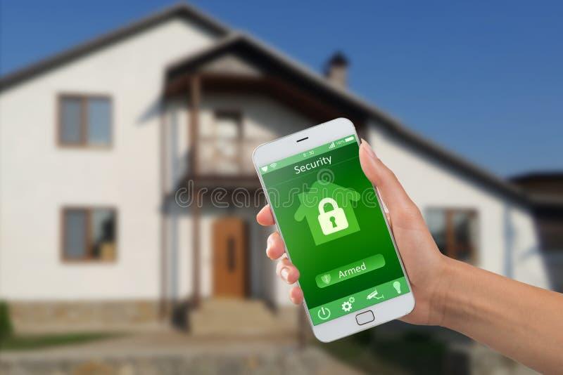 Smartphone con la seguridad en el hogar app en una mano en el fondo del edificio foto de archivo libre de regalías