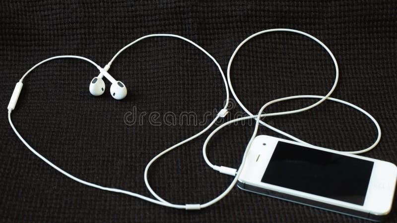 Smartphone con le cuffie che si trovano come un cuore su un tessuto strutturato scuro fotografia stock libera da diritti