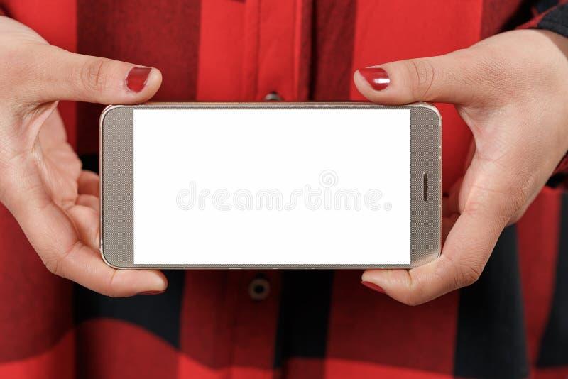 Smartphone con lo schermo bianco in bianco orizzontalmente in mani femminili Contro lo sfondo della ragazza rossa della camicia d fotografia stock
