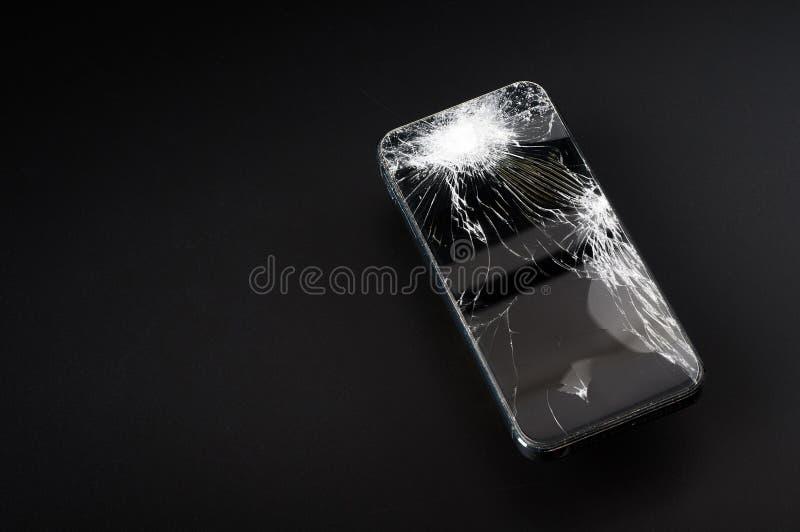 Smartphone con lo schermo rotto su fondo scuro fotografia stock libera da diritti