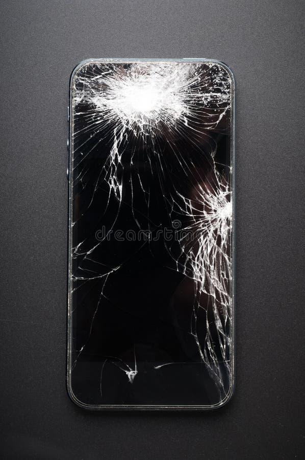 Smartphone con lo schermo rotto su fondo scuro immagini stock libere da diritti