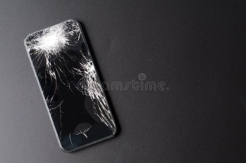 Smartphone con lo schermo rotto su fondo scuro fotografia stock