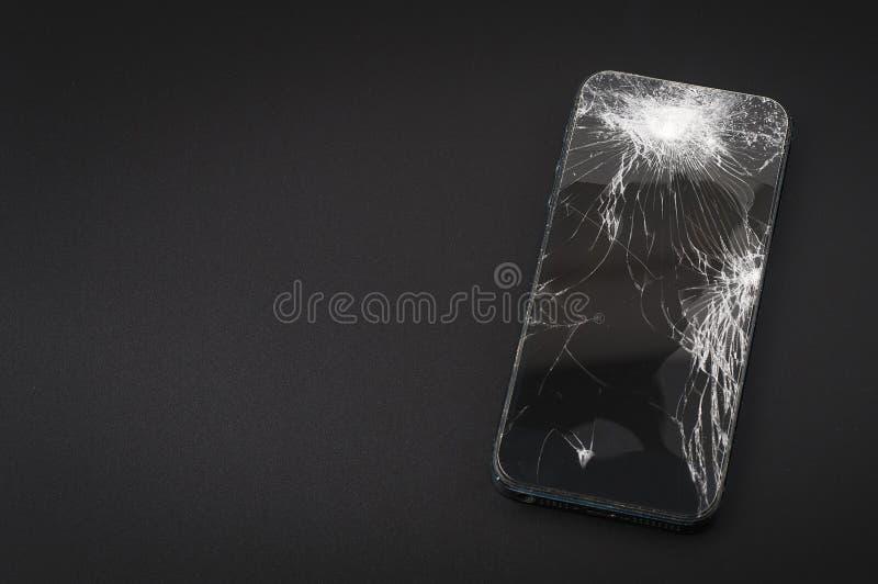 Smartphone con lo schermo rotto su fondo scuro immagini stock