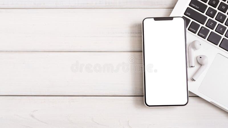 Smartphone con los auriculares blancos inalámbricos en el teclado del ordenador portátil fotografía de archivo libre de regalías